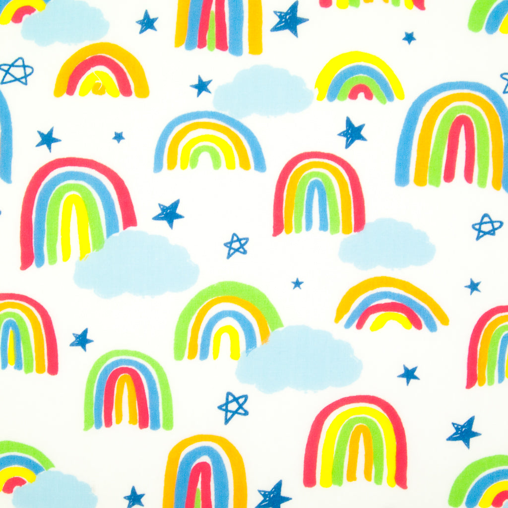 Brightly coloured childlike drawings of rainbows on a white polycotton fabric