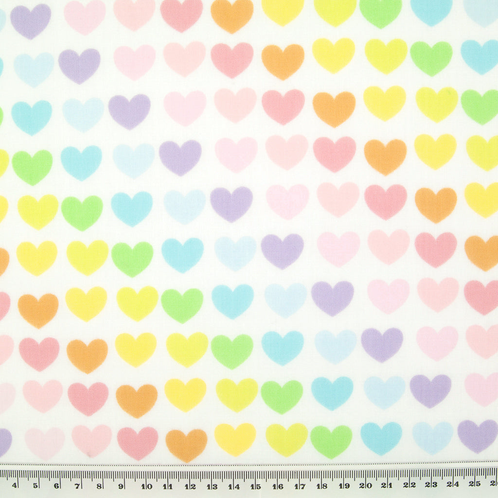 Lines of pastel hearts are printed on a fat quarter of white polycotton fabric with a ruler at the bottom for size perspective