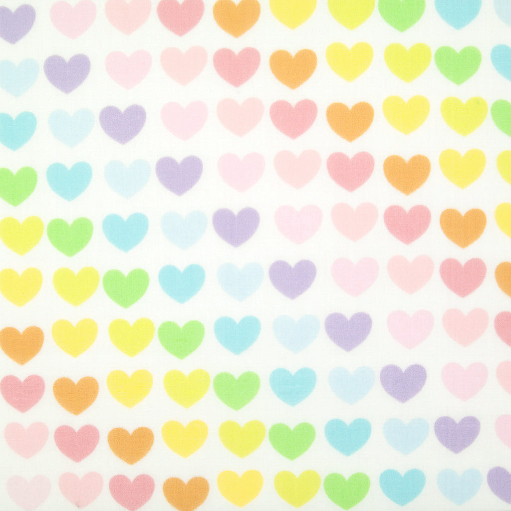 Lines of pastel hearts are printed on a fat quarter of white polycotton fabric