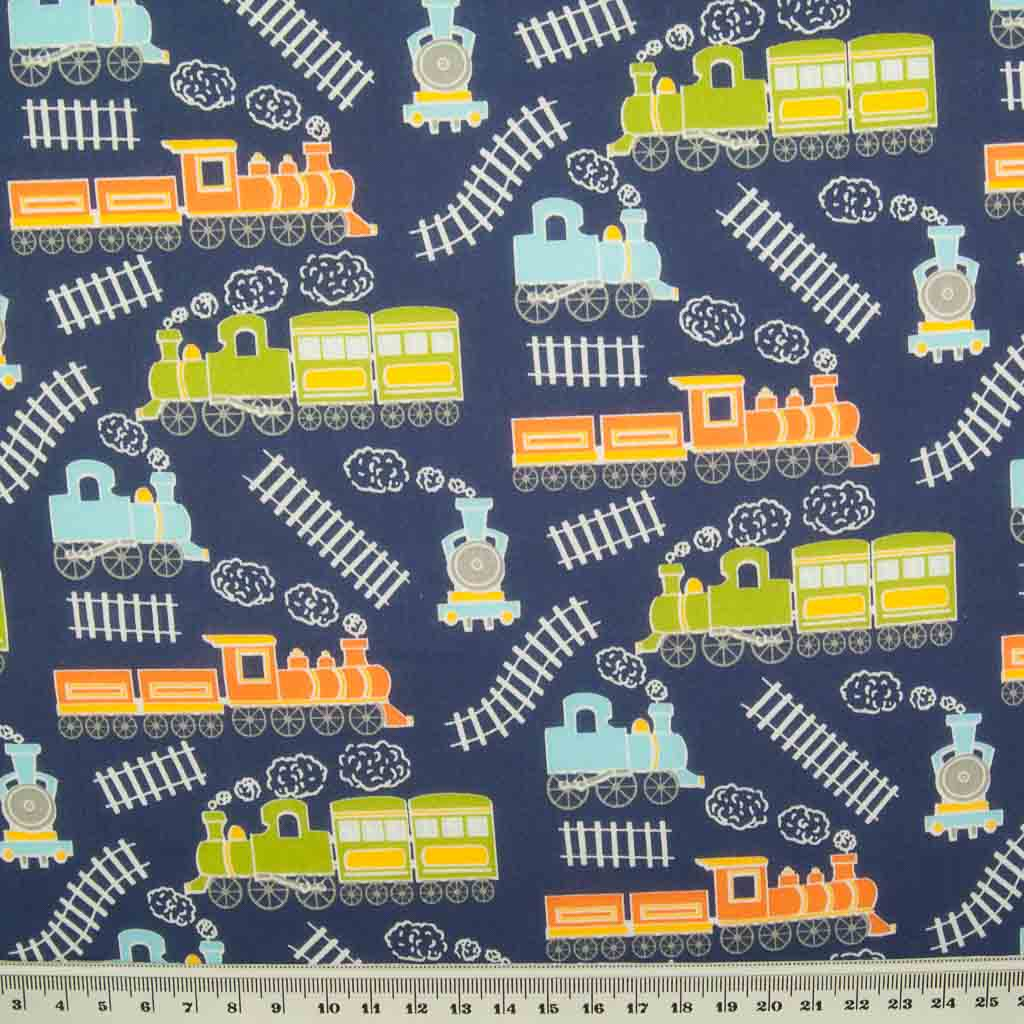 Green, blue and orange trains on train tracks are printed on a navy blue polycotton fabric with a ruler at the bottom for size perspective