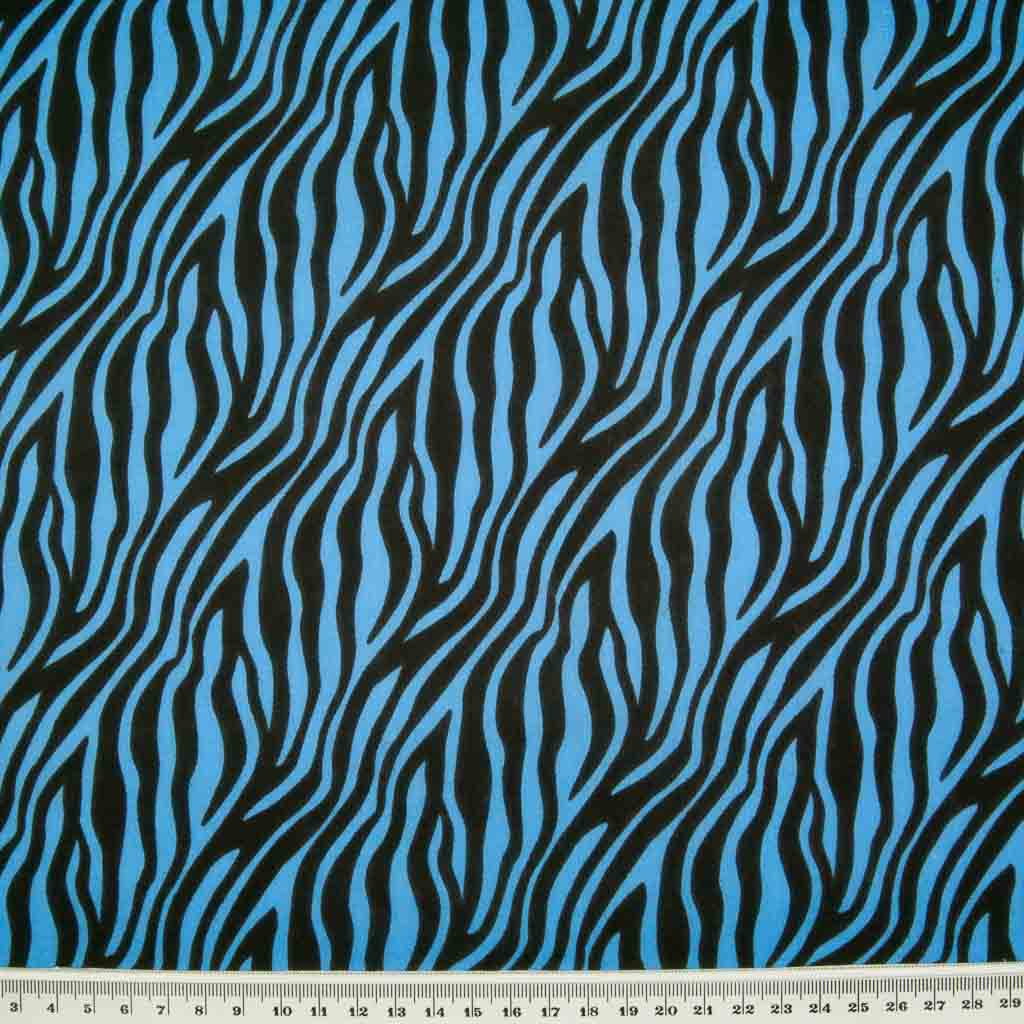 Zebra print polycotton fabric in blue and black with a ruler at the bottom for size perspective