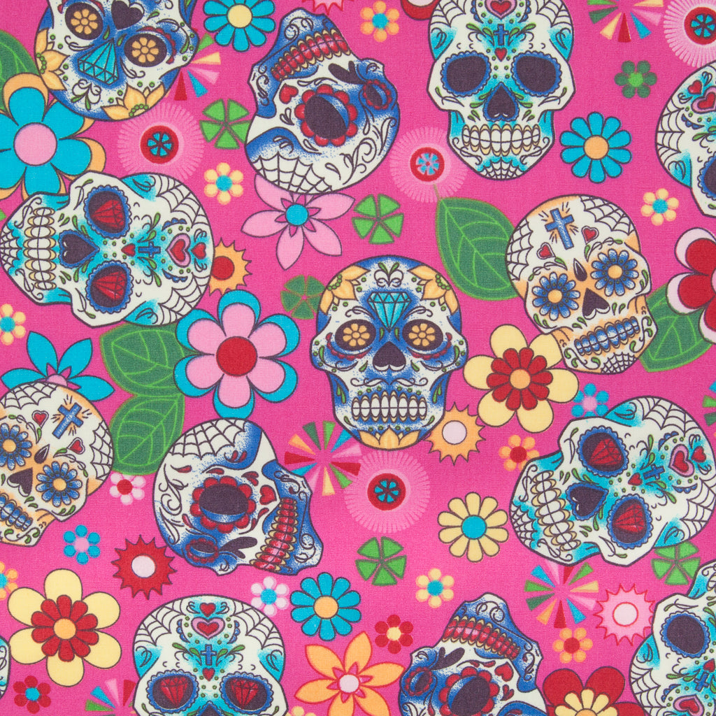 A Rose & Hubble cotton fabric with bright and colourful skulls and flowers printed on a cerise background