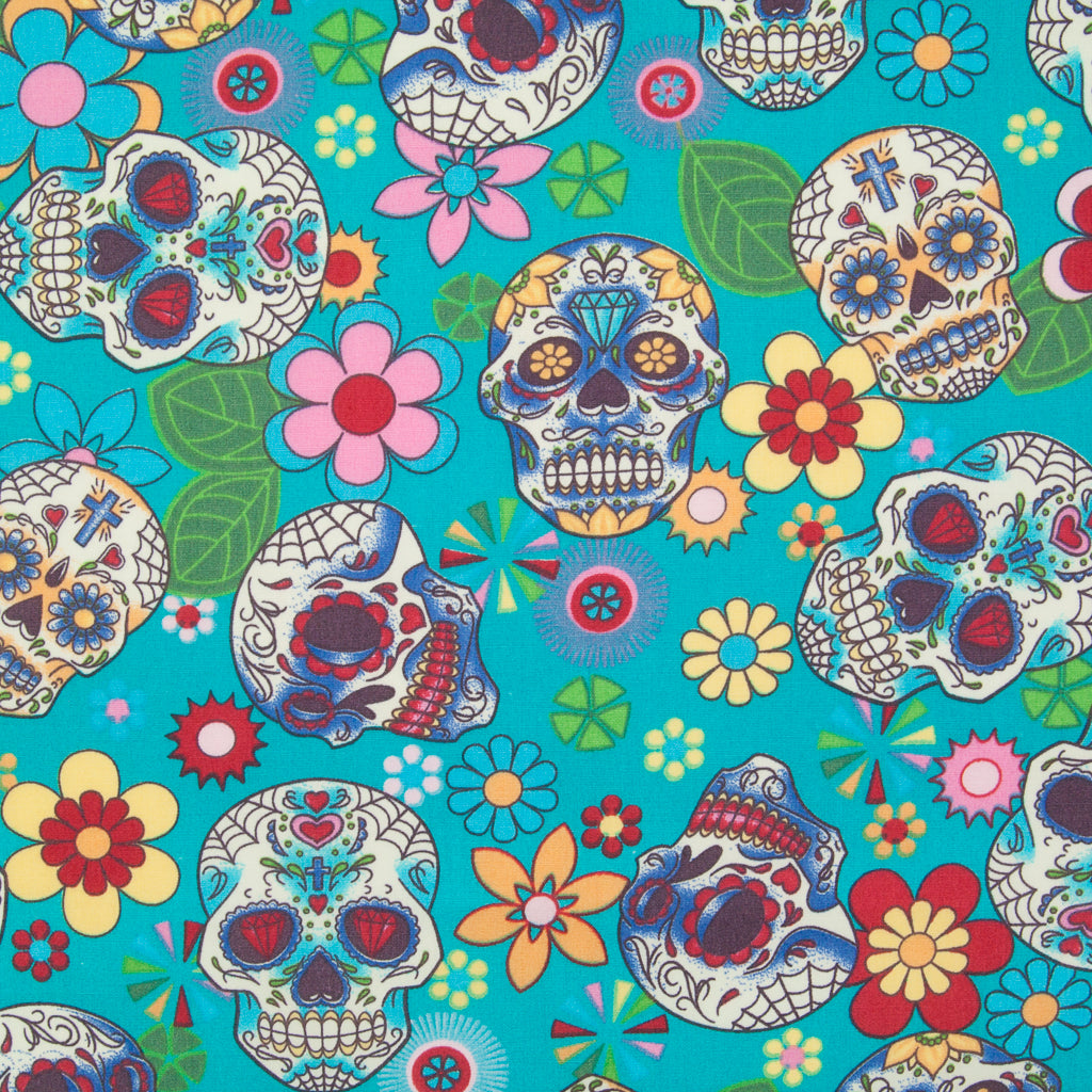 A Rose & Hubble cotton fabric with bright and colourful skulls and flowers printed on a turquoise background