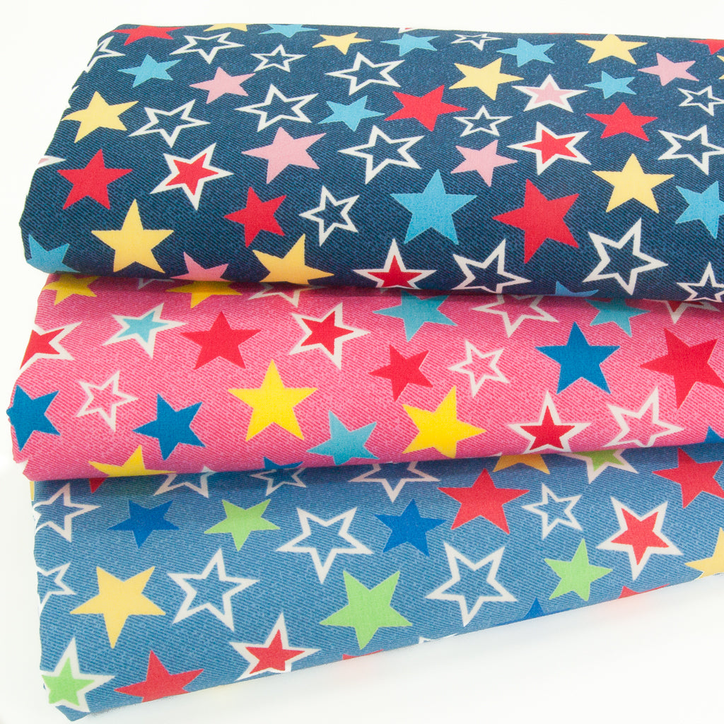 Three 100% cotton fabric prints of red, yellow and blue stars on pink and blue backgrounds stacked in a fat quarter bundle