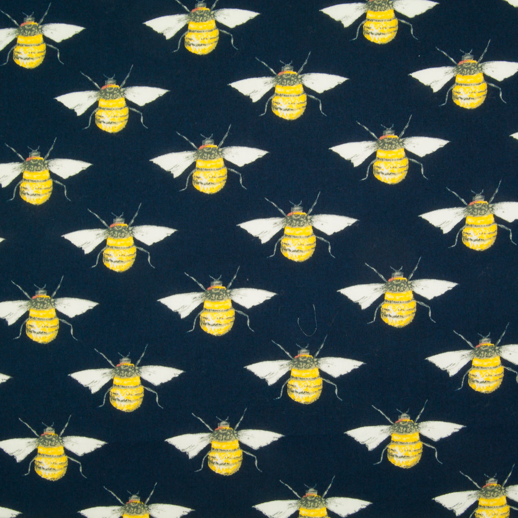 Large black and yellow bees in a geometric pattern on a flat piece of navy blue cotton poplin fabric