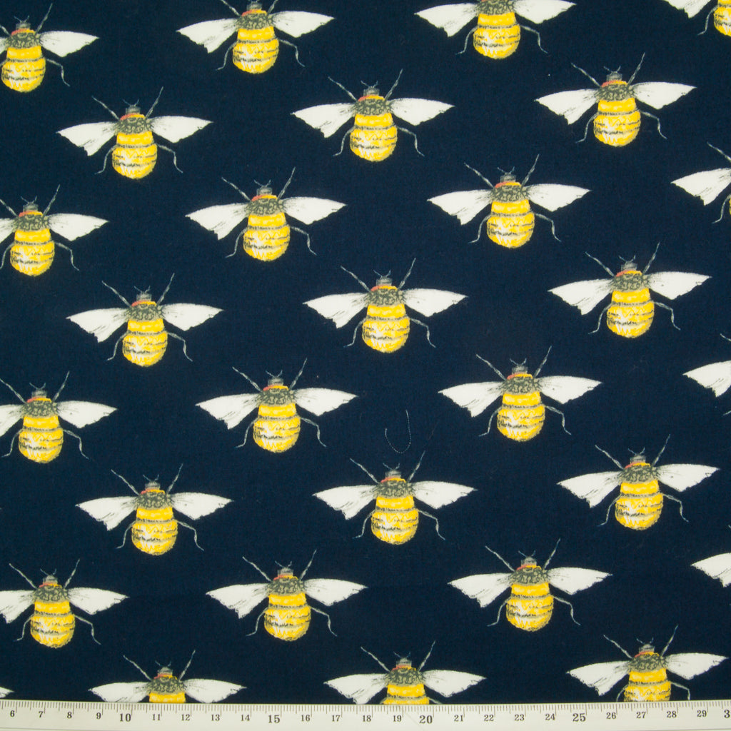 Large black and yellow bees in a geometric pattern on a flat piece of navy blue cotton poplin fabric with a ruler at the bottom for size perspective