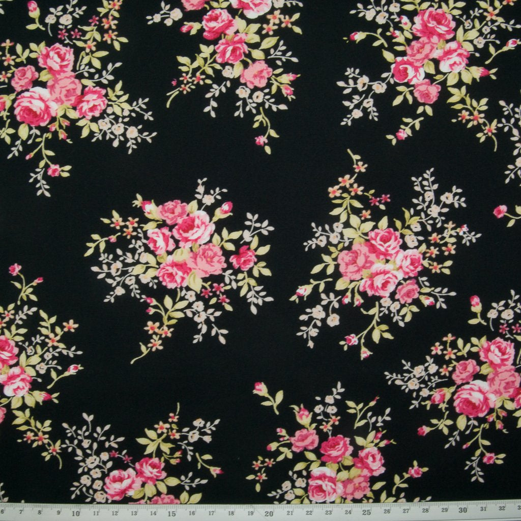 A fat quarter of small bouquets of pink roses on a black Rose & Hubble cotton poplin fabric with a ruler at the bottom for size perspective