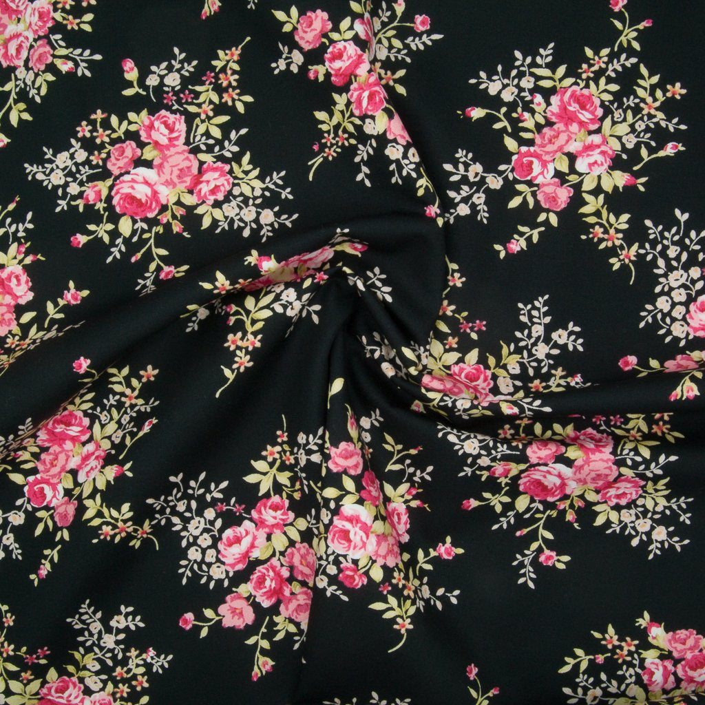 A fat quarter of small bouquets of pink roses on a black Rose & Hubble cotton poplin fabric in a swirl for drape perspective