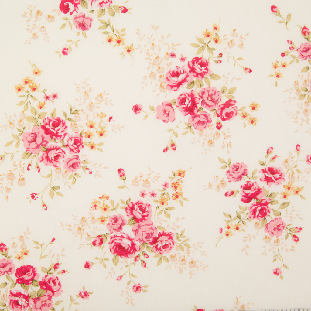 A fat quarter of small bouquets of pink roses on an ivory Rose & Hubble cotton poplin fabric