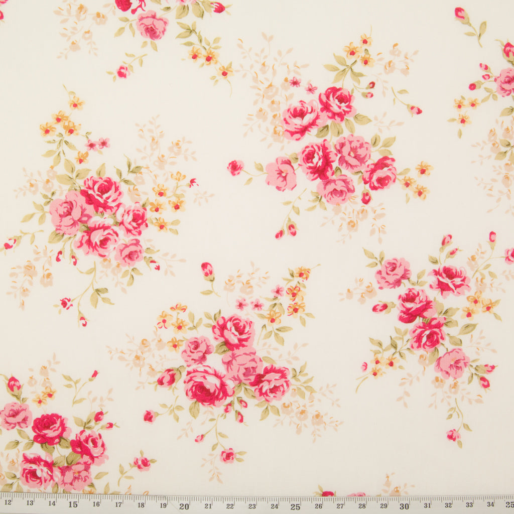 A fat quarter of small bouquets of pink roses on an ivory Rose & Hubble cotton poplin fabric with a ruler for size perspective