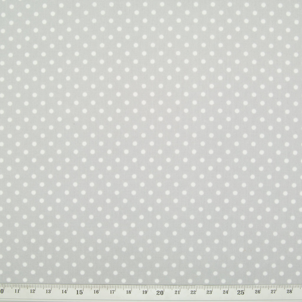Small white spots printed on a silver cotton fabric with ruler for perspective