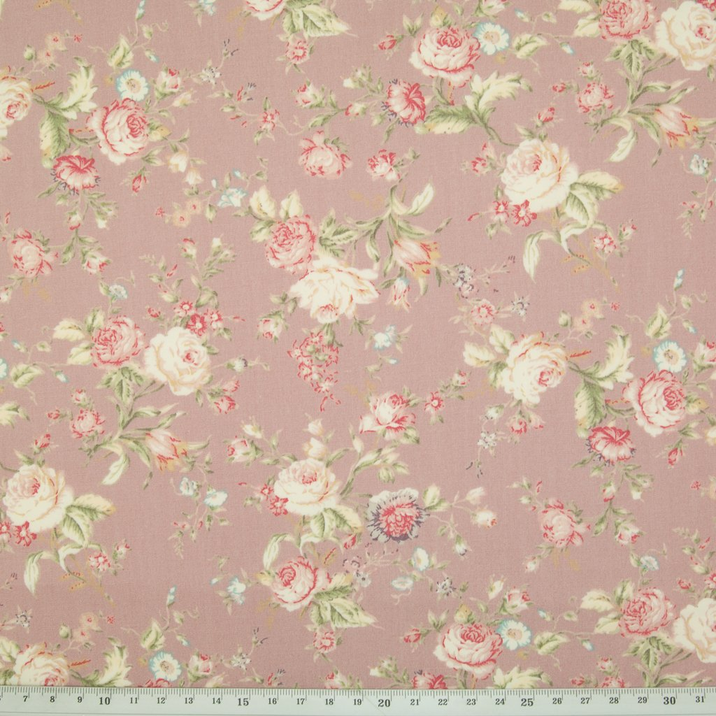 A floral pattern of pink and pale roses on a cotton poplin fabric with a cm ruler at the bottom for size perspective