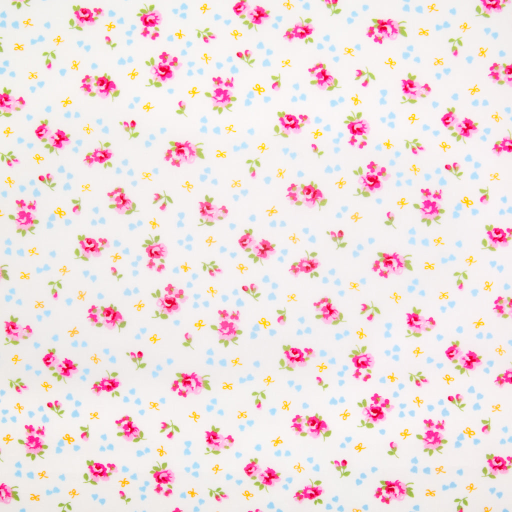 Small, single scattered pink roses with tiny blue hearts and ochre bows printed on a white Rose and Hubble cotton fabric pictured flat