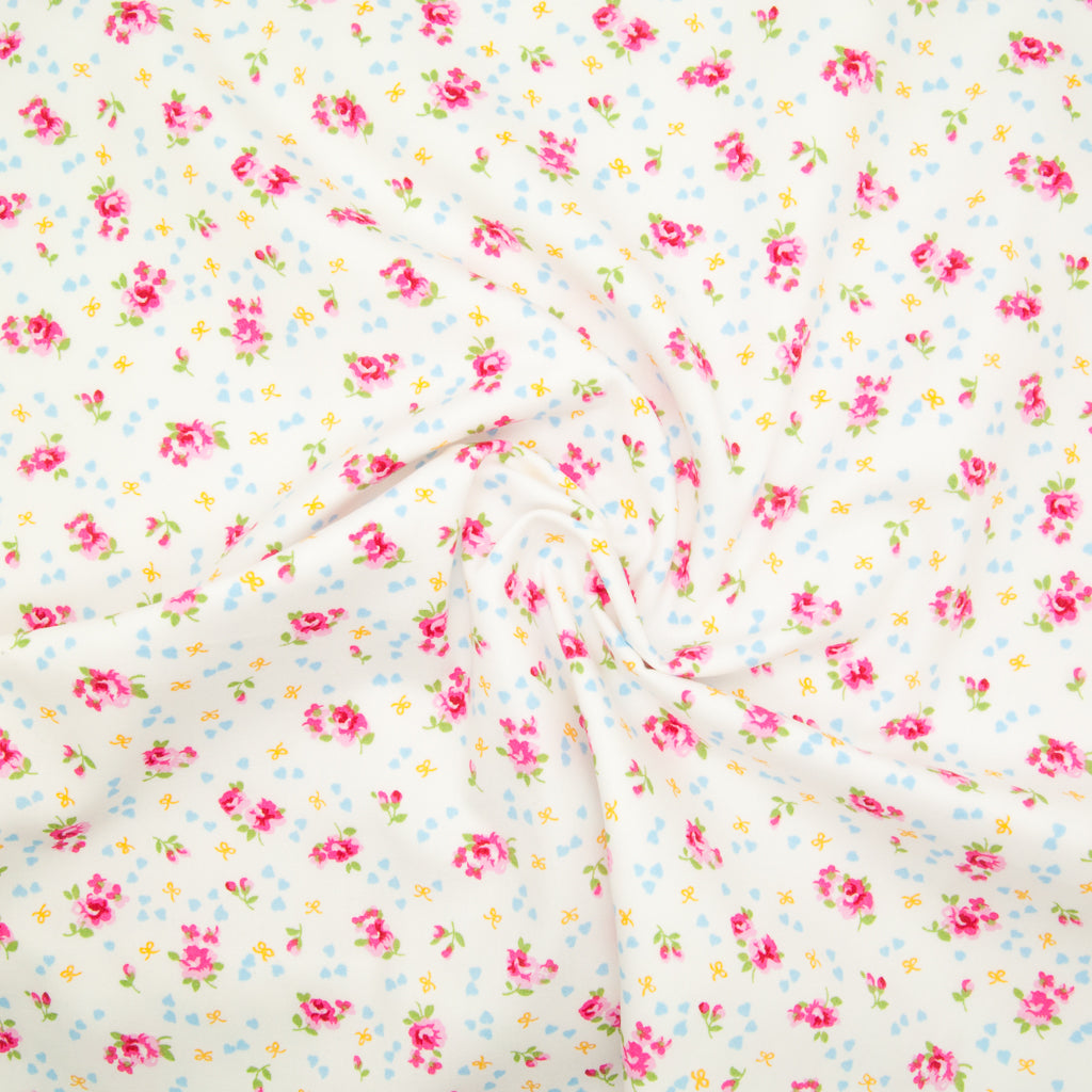 Rose and Hubble ditsy Alice rose on white cotton fabric pictured in a swirl for drape perspective