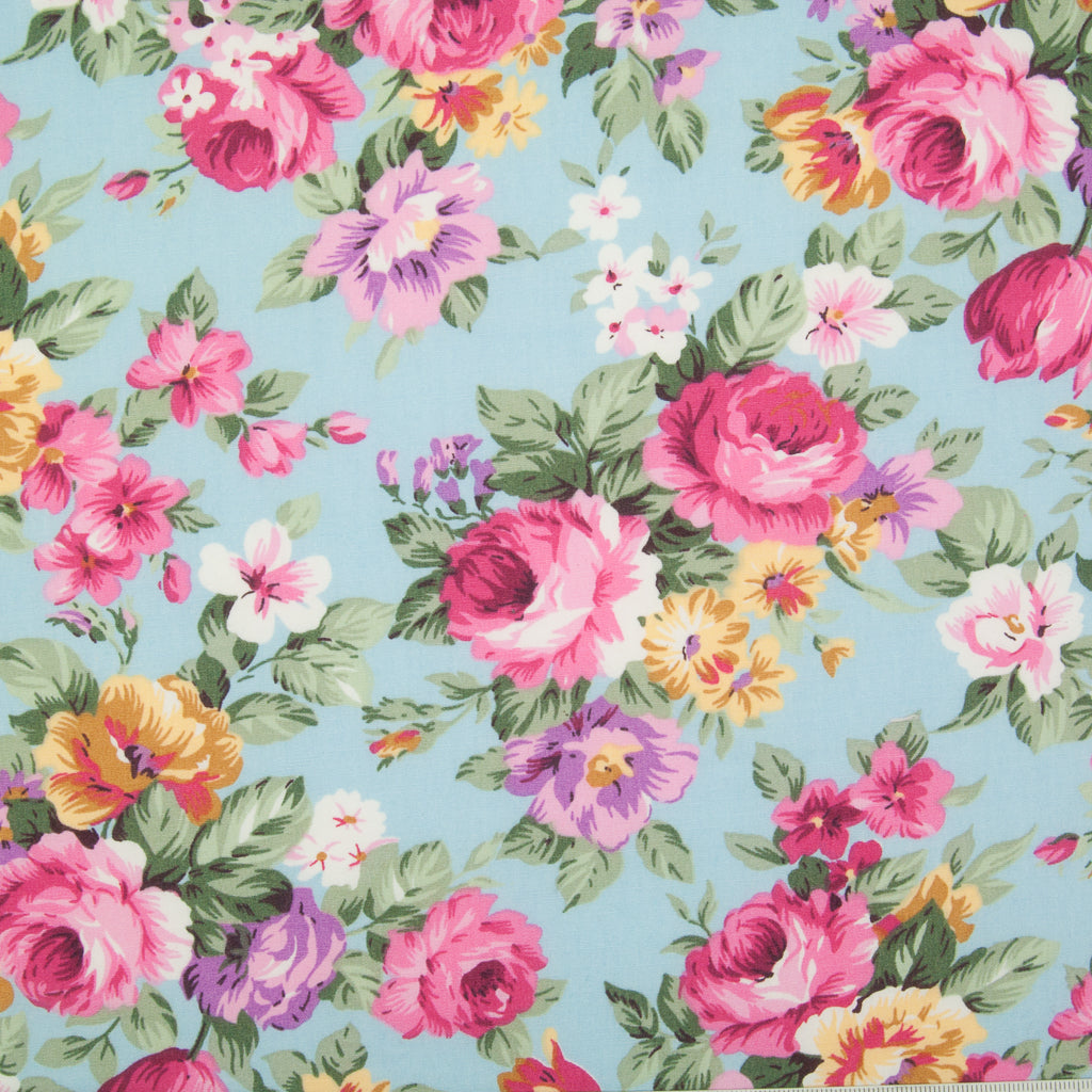 Bunches of large pink roses with lilac and yellow flowers on a sky blue Rose and Hubble cotton poplin fabric pictured flat