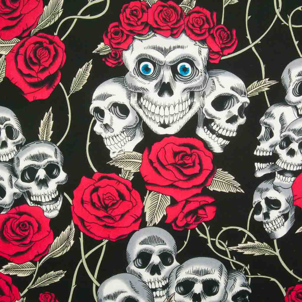 Gothic white skulls with blue eyes crowned with bright red roses are printed on a black 100% cotton poplin fabric by Rose and Hubble