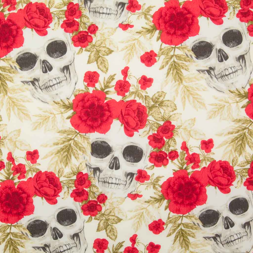 White skulls appear through a bed of red roses all printed on a n ivory 100% cotton poplin fabric by Rose and Hubble