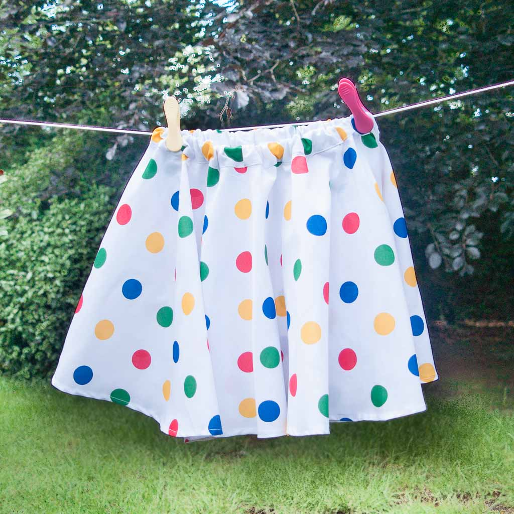 A full circle skirt in rainbow spots polycotton hanging on a washing line