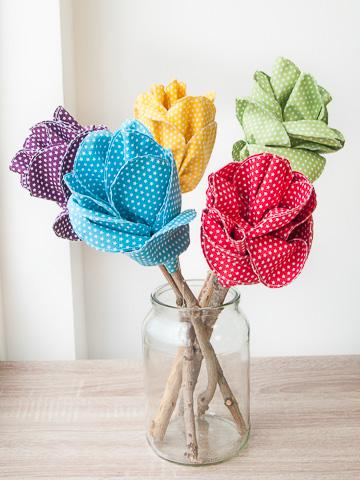 Five brightly coloured flowers made with starry fabric in a glass vase