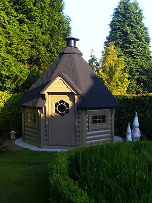 finnish bbq hut placed in the beautiful backyard garden