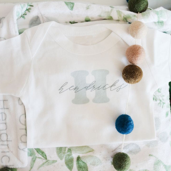 baby name reveal onesie flatlay