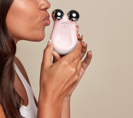 Woman holding a NuFACE Mini with both hands puckering her lips.