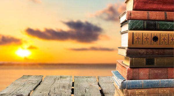 Summer Books Stacked by Sunset - ISA Professional