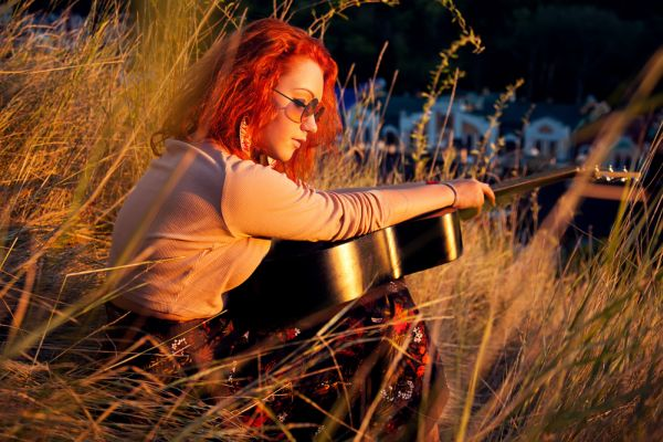 Redhead Playing Guitar In Nature ISA Professional