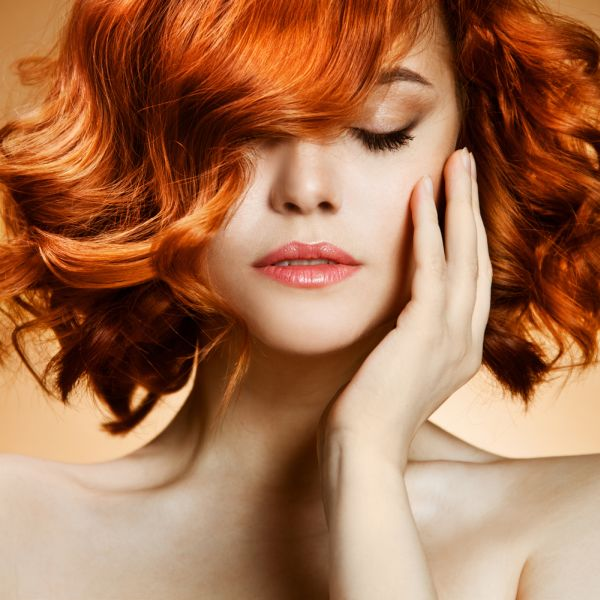 Short Wavy Haired Redhead Woman Touching Her Cheek ISA Professional