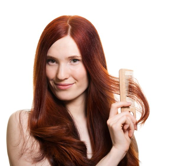 Red Haired Woman Combing Hair Away From Face ISA Professional