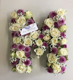 A New born Initial with spray roses