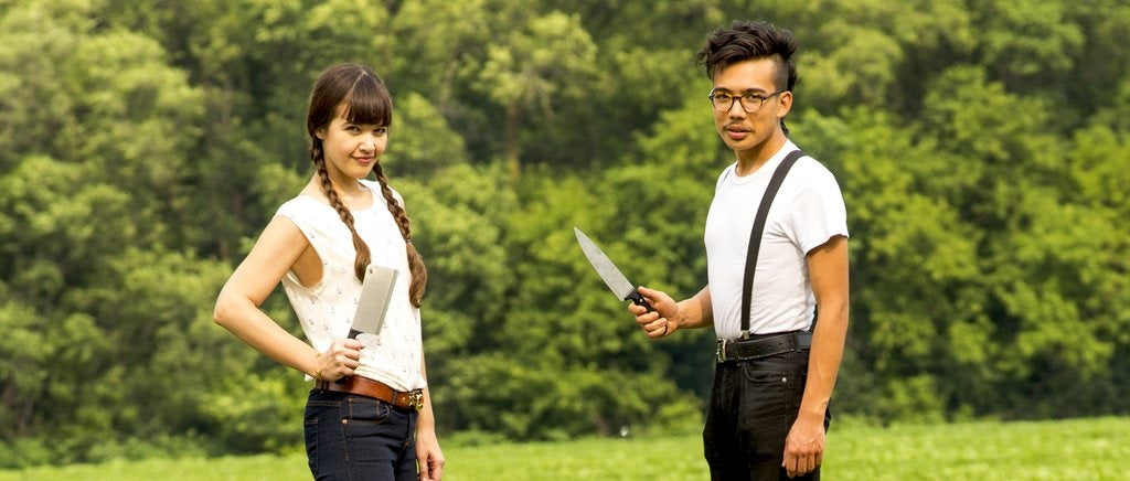 two people standing in a field and holding butcher knives