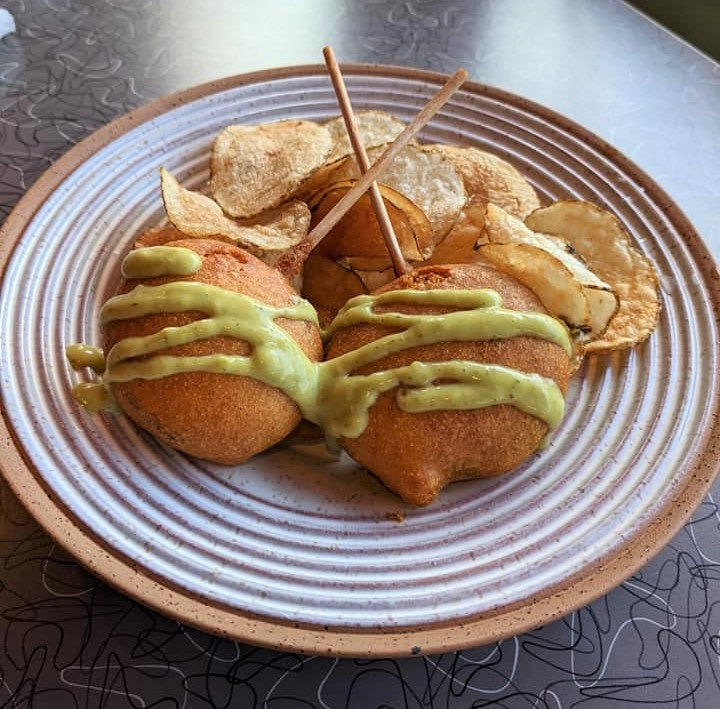 two corn dog pop drizzled with green sauce and a side of potato chips