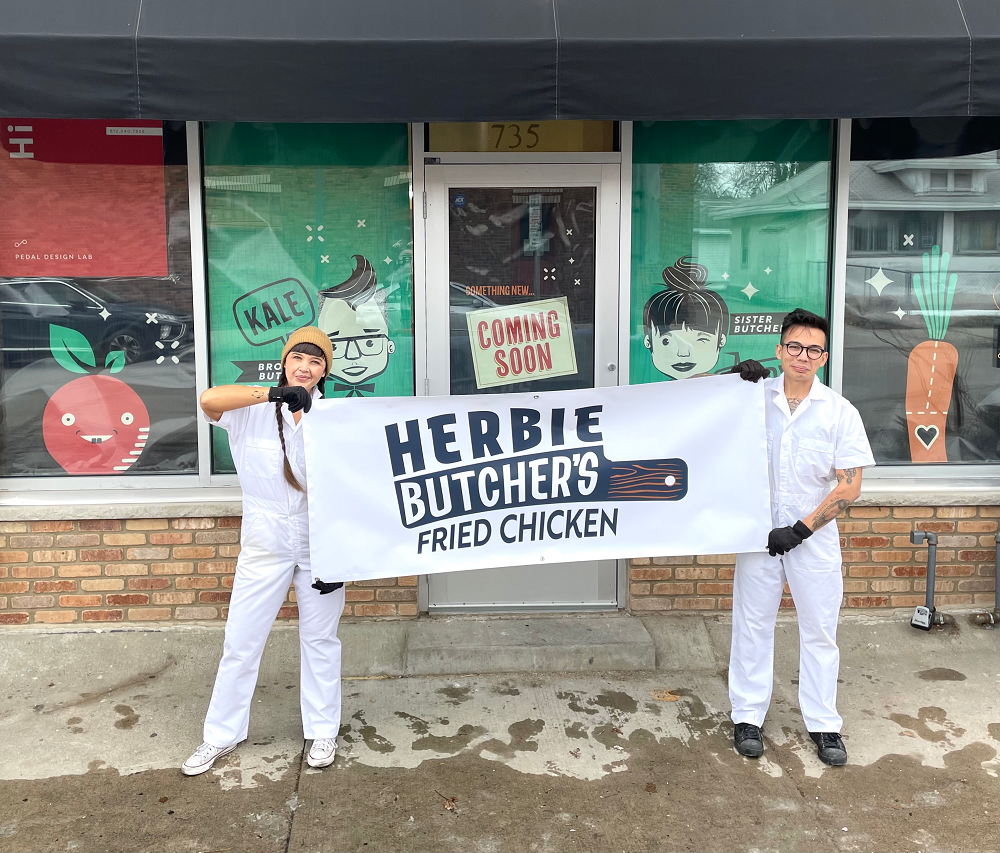 two people holding a sign for Herbie Butcher's Fried Chicken