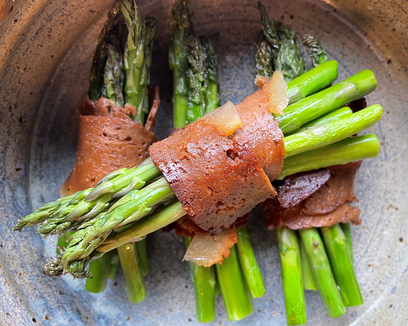 a bundle of asparagus wrapped in vegan bacon