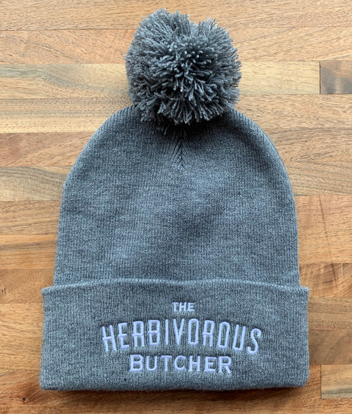 gray beanie with The Herbivorous Butcher logo in white. Has a gray puff on top