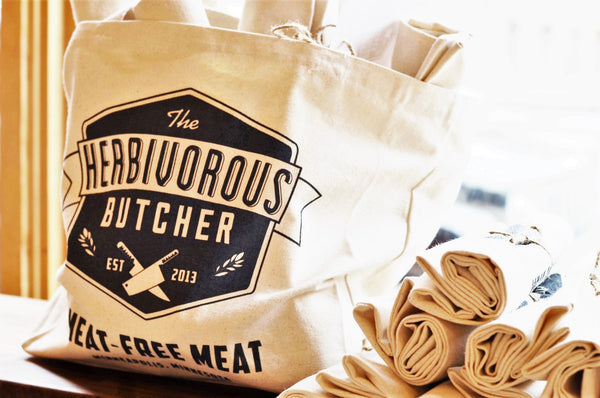 cream canvas tote with The Herbivorous Butcher logo on it
