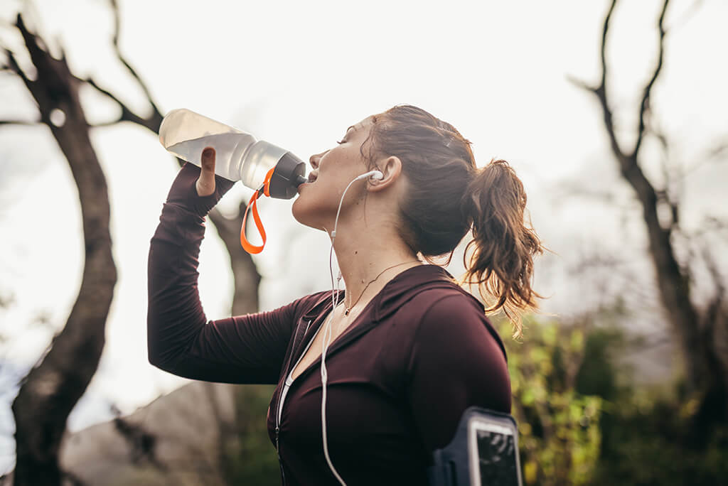 girl drinking from a sports bottle