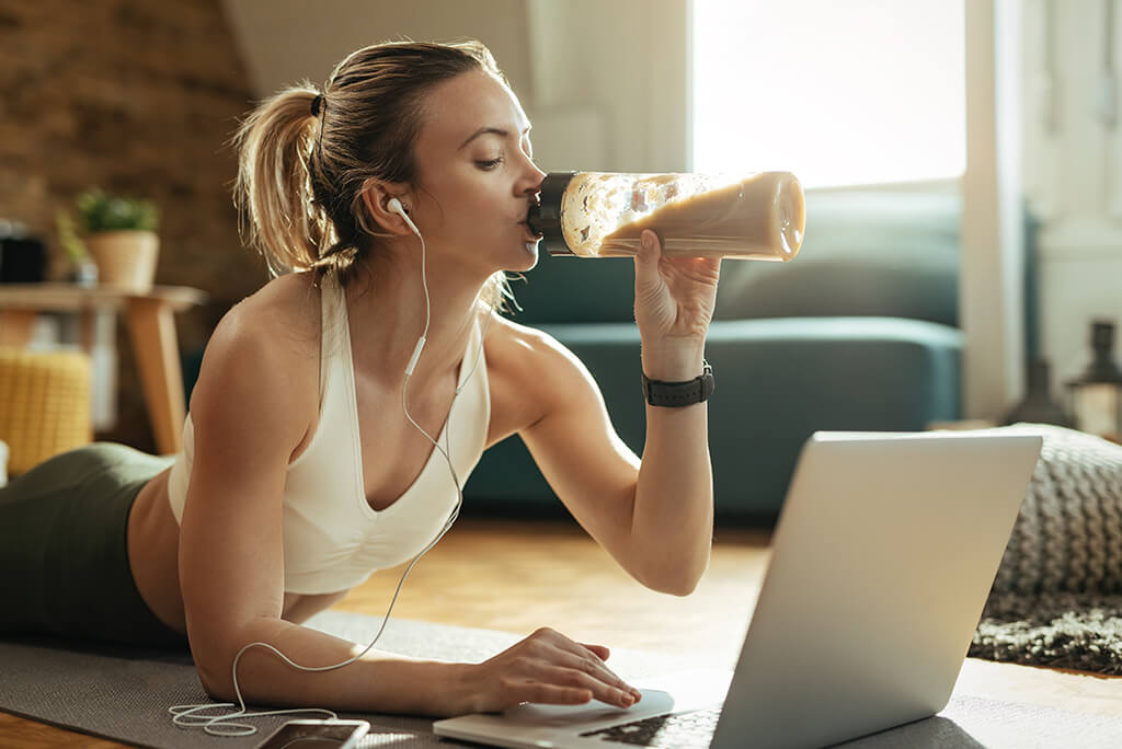 girl drinking a smoothie while working