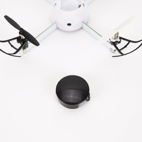 White drone and black batter on a white background. Extra battery for your drone kit. More power with four minutes of continuous flight time.