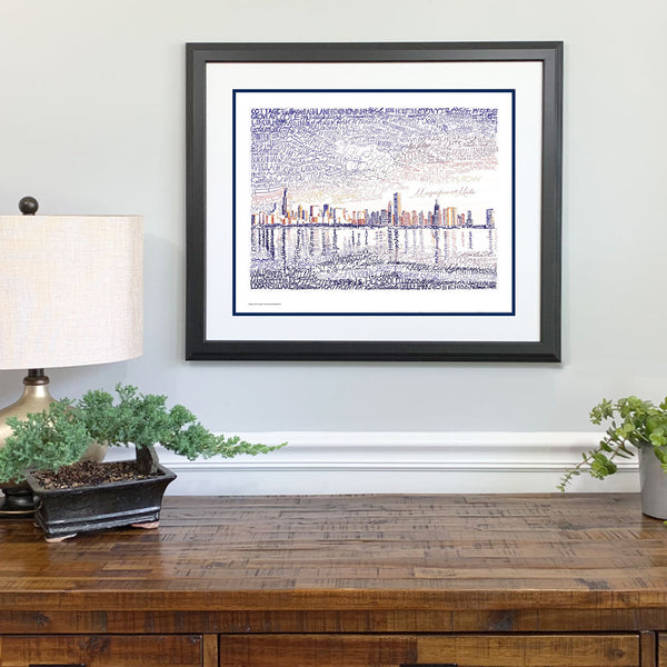 Framed word art view of Chicago skyline, handwritten with names of streets and neighborhoods, hangs on wall.
