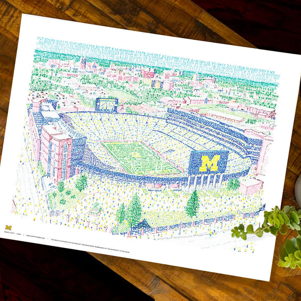 Unframed word art print depicting Michigan Stadium, handwritten with stats of 440 Wolverines wins, lies flat on table.