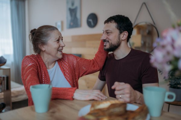 Older mother touches side of her adult male child's face while both sit at kitchen table, mugs and flowers visible.