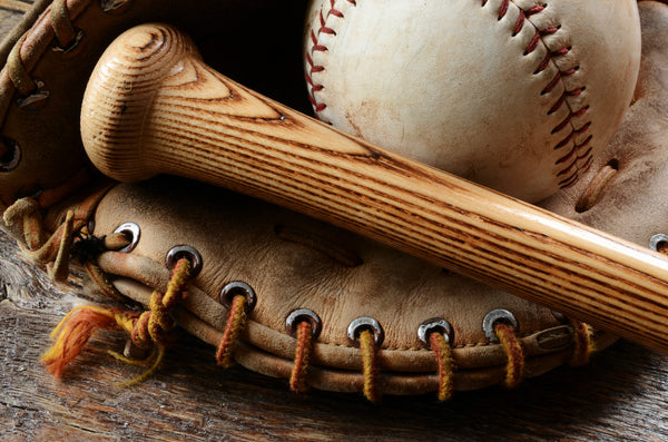 Tip and handle of wooden baseball bat and old baseball rest in a leather baseball glove.