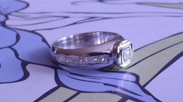 HALF ETERNITY WITH BEZEL SET CENTRE DIAMOND AND CHANNEL SET SIDES ENGAGEMENT RING