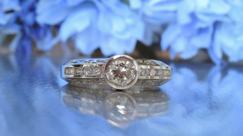 SCROLL DESIGN CHANNEL SET HALF ETERNITY ENGAGEMENT RING WITH BEZEL SET CENTRE