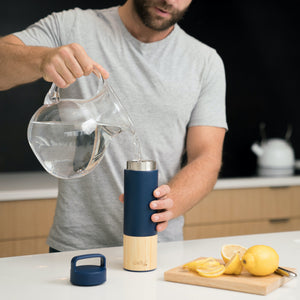 Man Pouring Clean Water and Lemon Into Insulated Bamboo Water Bottle