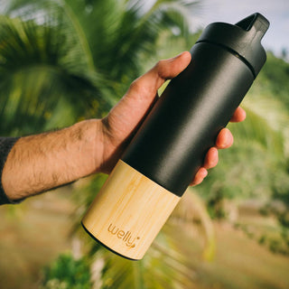 Black Adventure Bundle, Blue Adventure Bundle, Rose Adventure Bundle, Mint Adventure Bundle, White Adventure Bundle, Man holds black water bottle with bamboo base in front of palm trees
