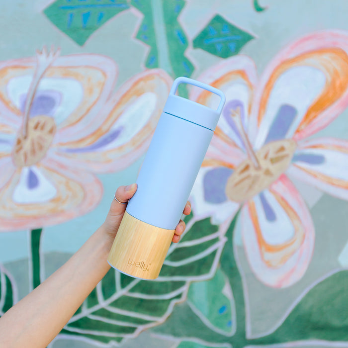 Tall pale blue water bottle held in front of pastel floral mural