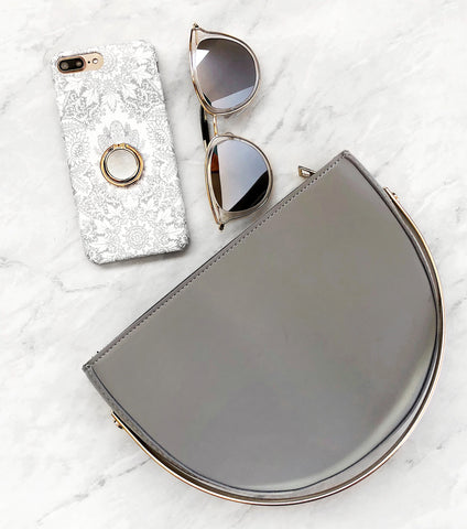 gray and gold accessories circle bag and sunnies